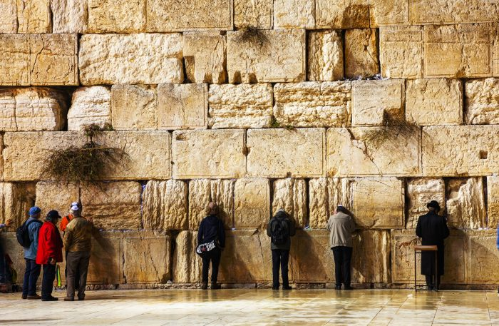 JERUSALEM - DECEMBER 15: The Western Wall in the night with a praying pilgrims on December 15, 2013 in Jerusalem. It's located in the Old City of Jerusalem at the foot of the western side of the Temple Mount.
