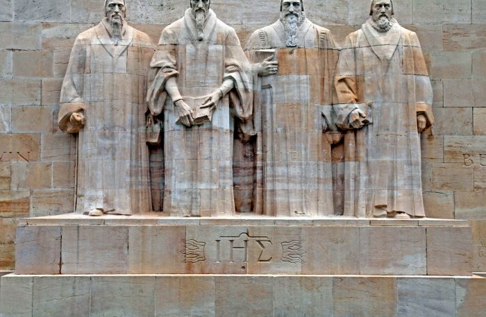 Reformation wall in Parc Des Bastions, Geneva, Switzerland. Sculptures of the four great figures of the geneva protestant movement : Guillaume Farel (1489 - 1565), Jean Calvin (1509-1564), Theodore de Beze (1513-1605) and John Knox (1513-1572) , Geneva, Switzerland.